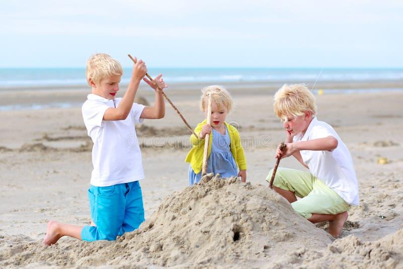 Lyckliga ungar som spelar med sand på stranden fotografering för bildbyråer