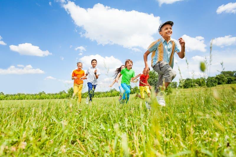 Lyckliga ungar som spelar och kör i fältet arkivfoto