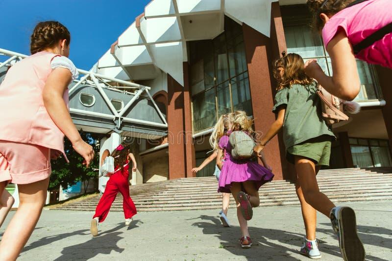 Lyckliga ungar som spelar på stads gata i soliga sommars dag arkivfoton
