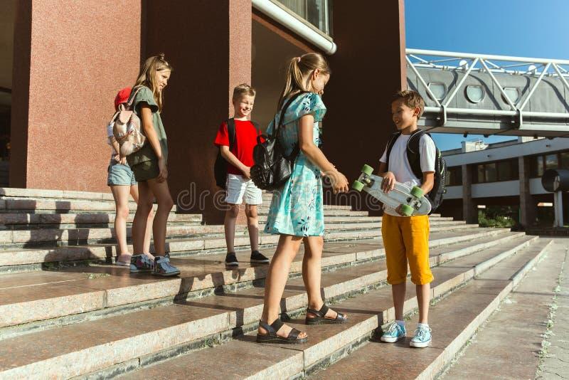 Lyckliga ungar som spelar på stads gata i soliga sommars dag fotografering för bildbyråer
