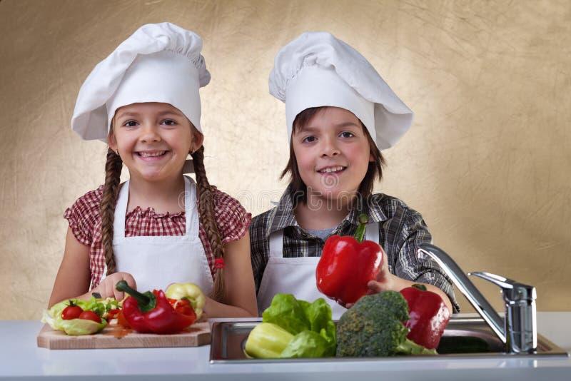 Lyckliga ungar som tvättar grönsaker för en sallad royaltyfri fotografi