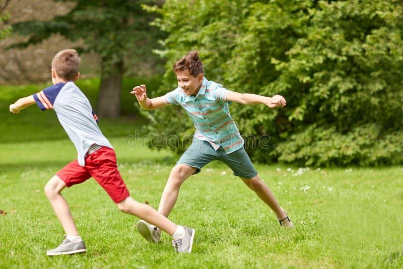 Lyckliga ungar som utomhus kör och spelar som är modig arkivfoto