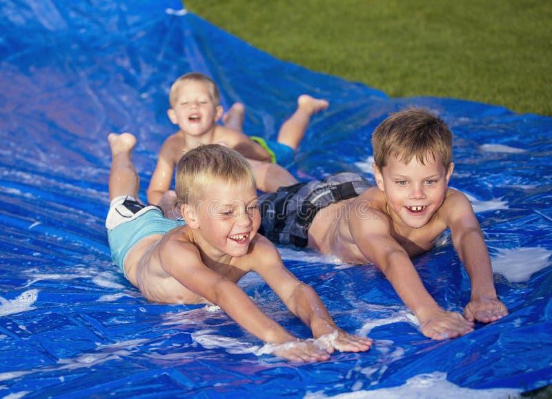 Lyckliga ungar som utomhus spelar på en snedsteg och en glidbana arkivbilder