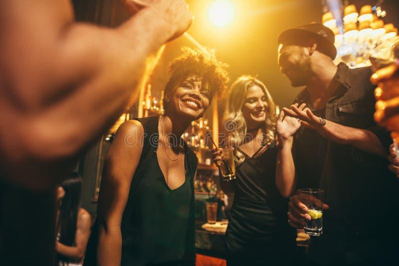 Lyckliga ungdomarsom har gyckel en nattklubb royaltyfri fotografi