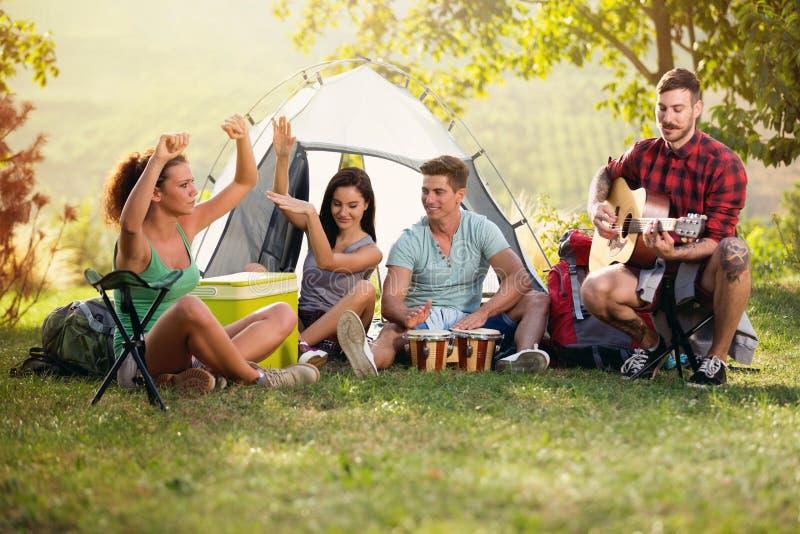 Lyckliga ungdomarsom har gyckel med musik på campa tur royaltyfri bild