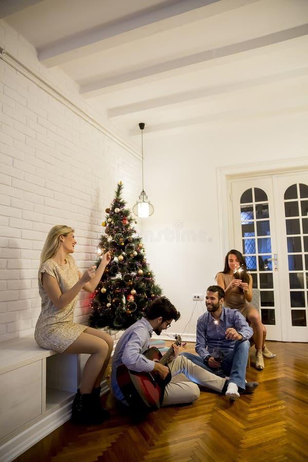 Lyckliga ungdomarsom hemma firar jul och nytt år vid gran-trädet och spelar den akustiska gitarren royaltyfri fotografi