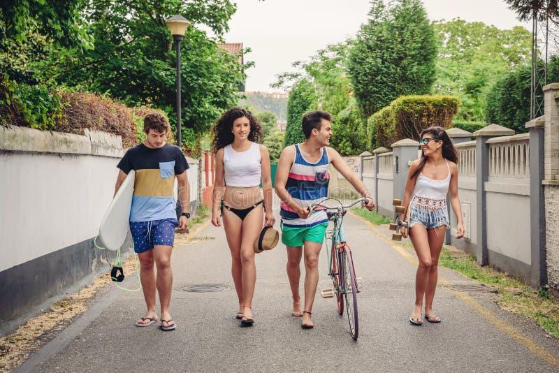 Lyckliga ungdomarsom promenerar vägen i sommardag fotografering för bildbyråer
