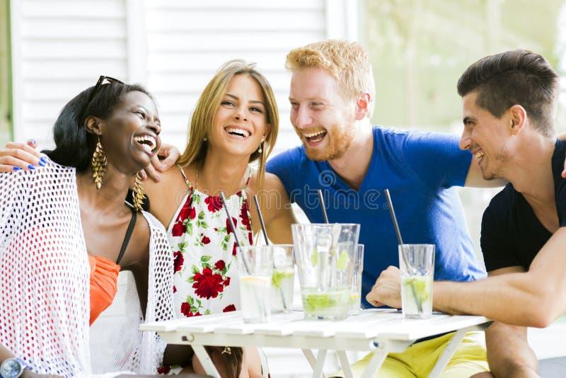 Lyckliga ungdomarsom skrattar en being som är lycklig på en tabell royaltyfria bilder