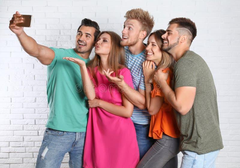 Lyckliga ungdomarsom tar selfie nära vit tegelsten royaltyfria bilder