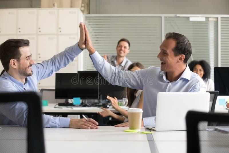 Lyckliga upphetsade manliga kollegor som ger högt fem på arbete arkivfoton