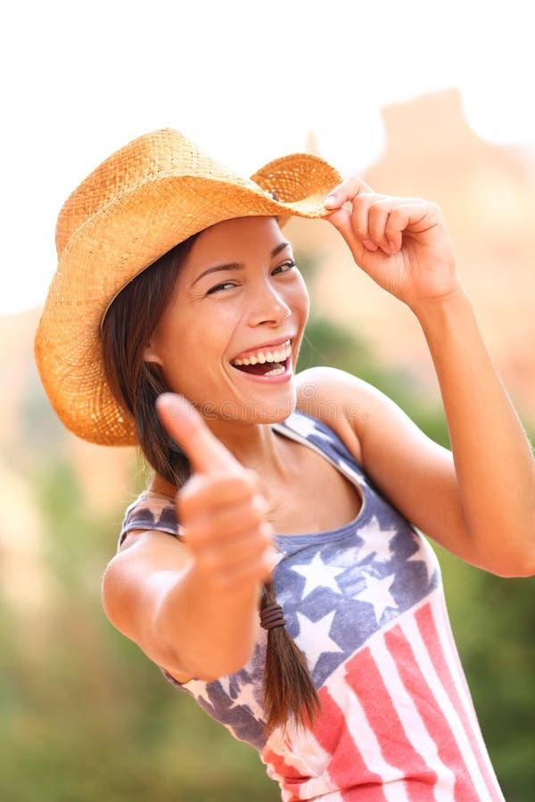 Lyckliga upphetsade tummar för amerikansk cowgirlkvinna upp royaltyfria foton