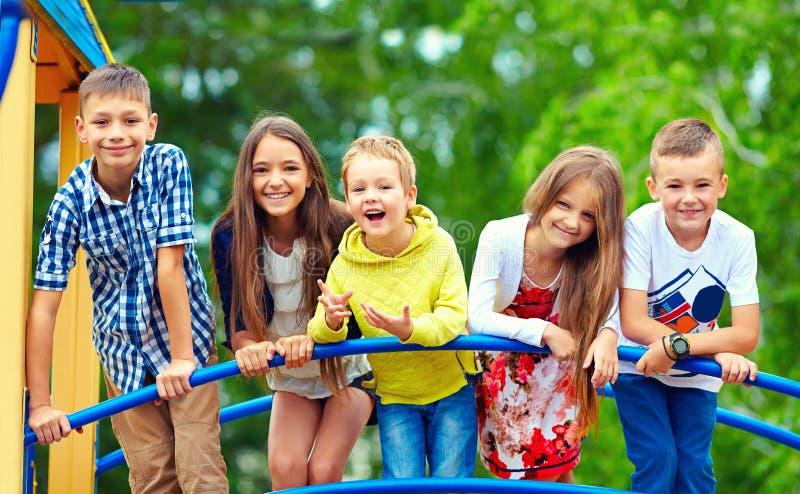 Lyckliga upphetsade ungar som har gyckel tillsammans på lekplats royaltyfri bild
