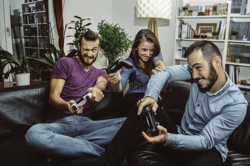 Lyckliga upphetsade vänner som hemma spelar videospel tillsammans och har gyckel royaltyfria foton