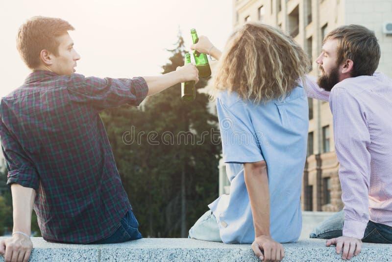 Lyckliga vänjubel med utomhus- öl royaltyfri fotografi