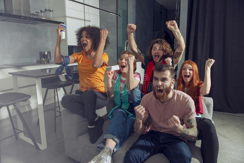 Lyckliga vänner av fotbollsfan som håller ögonen på fotboll på tv och firar seger arkivbild