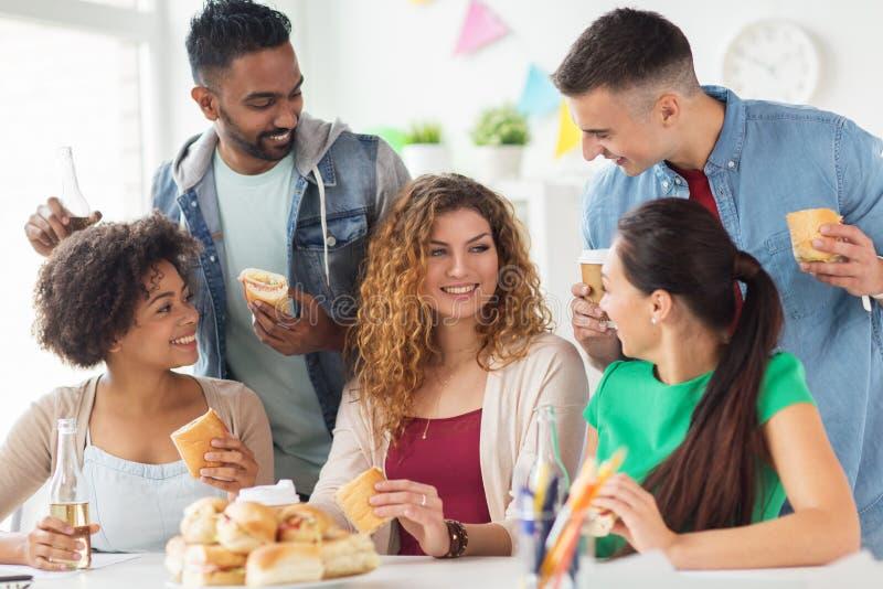 Lyckliga vänner eller lag som äter på kontorspartiet arkivfoto