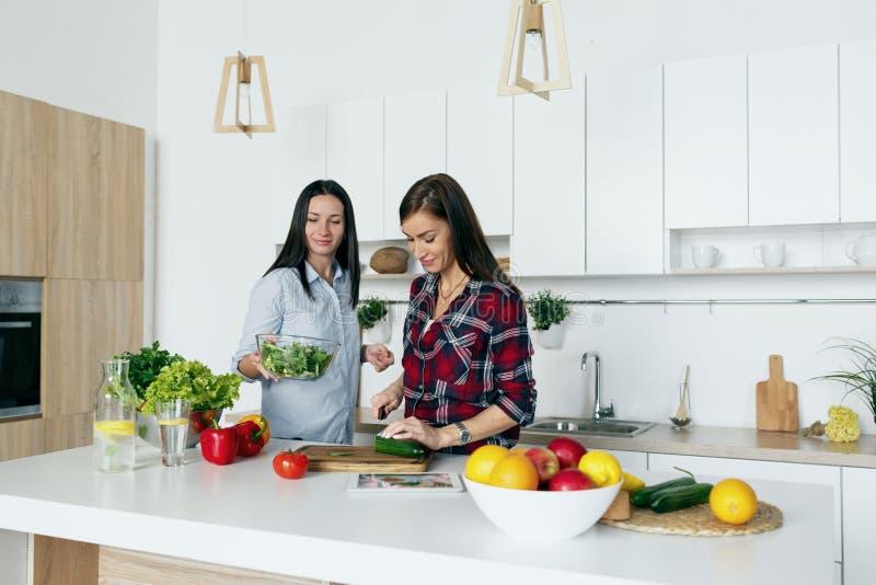 Lyckliga vänner för sund livsstil som talar laga mat grönsakhem K fotografering för bildbyråer