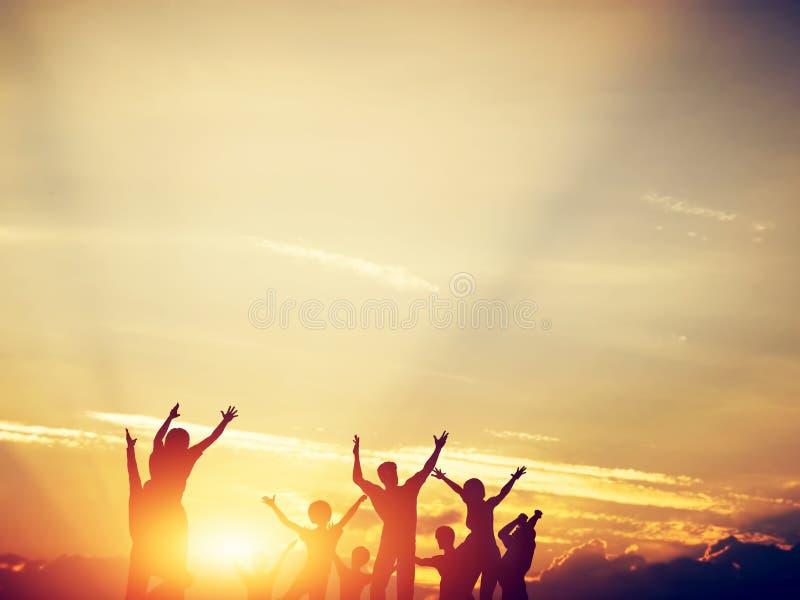 Lyckliga vänner, familj som tillsammans hoppar på solnedgången