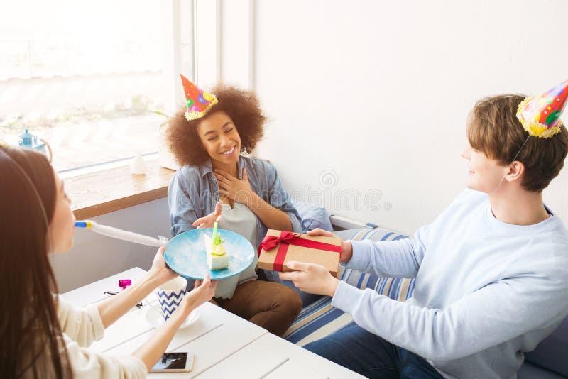Lyckliga vänner firar födelsedag De har roliga hattar på deras huvud Grabben rymmer en gåva medan flickan in royaltyfri bild