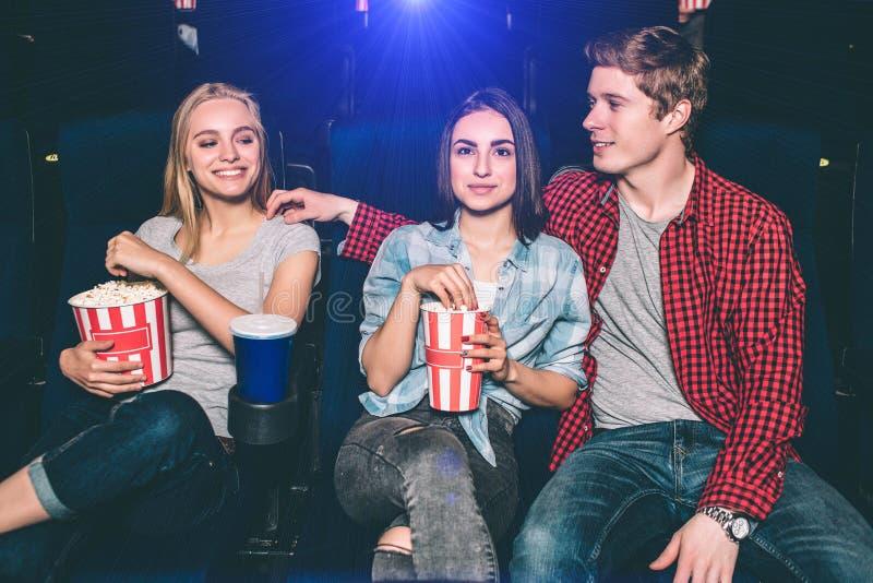 Lyckliga vänner håller ögonen på film De sitter tillsammans Grabben ser den blonda flickan Hon är lycklig om det fotografering för bildbyråer