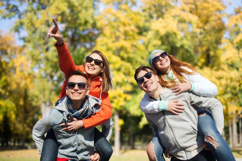 Lyckliga vänner i skuggor som har gyckel på hösten, parkerar royaltyfri bild