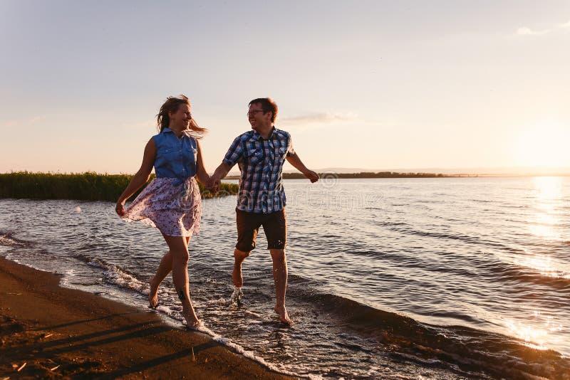 Lyckliga vänner kör på stranden arkivbilder