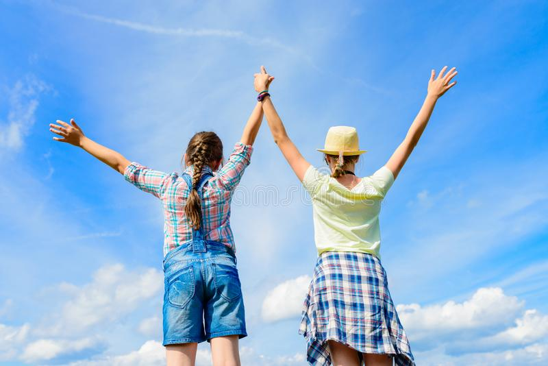 Lyckliga vänner med öppna armar under blå himmel royaltyfri foto