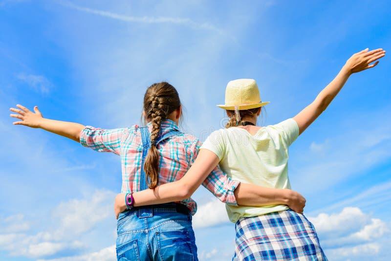 Lyckliga vänner med öppna armar under blå himmel royaltyfria bilder
