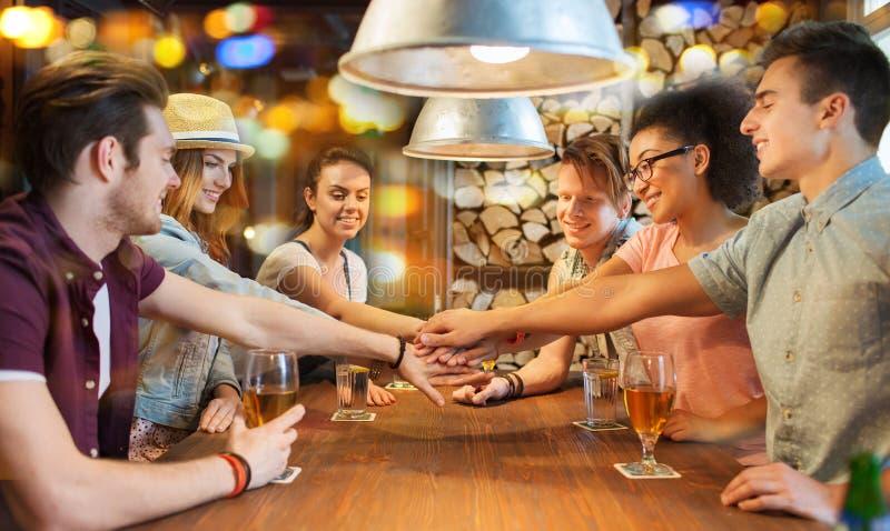 Lyckliga vänner med drinkar och händer överst på stången royaltyfri foto