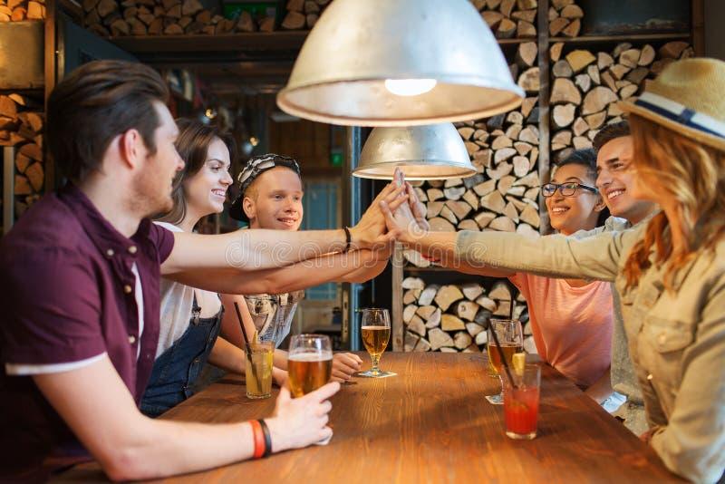 Lyckliga vänner med drinkar som gör höjdpunkt fem på stången arkivfoto