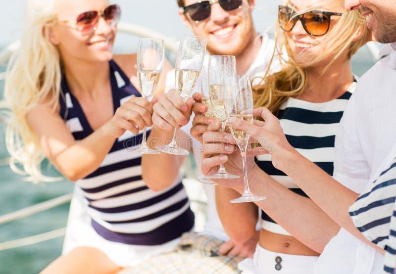 Lyckliga vänner med exponeringsglas av champagne på yachten royaltyfria bilder