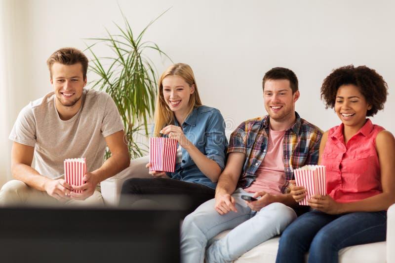 Lyckliga vänner med hållande ögonen på tv för popcorn hemma arkivbild