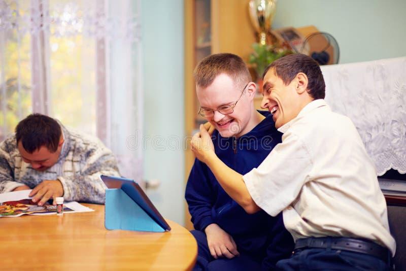 Lyckliga vänner med handikapp som umgås till och med internet arkivfoto