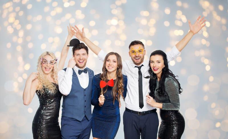 Lyckliga vänner med partistöttor som poserar över ljus arkivfoto