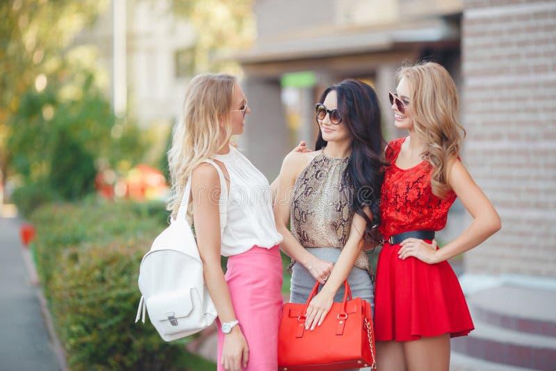 Lyckliga vänner med shoppingpåsar som är klara till att shoppa royaltyfria foton