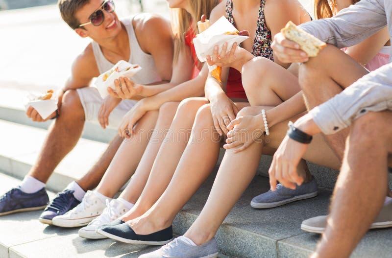 Lyckliga vänner som äter för avhämtning snabbmat i stad arkivbild