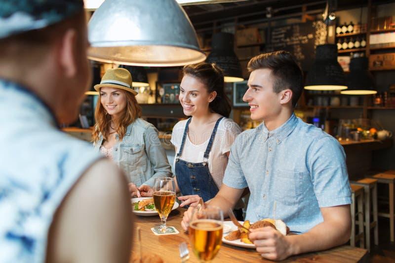 Lyckliga vänner som äter och dricker på stången eller baren royaltyfri bild