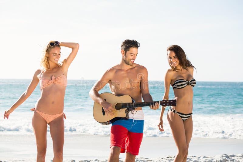 Lyckliga vänner som dansar och spelar gitarren på stranden royaltyfri fotografi