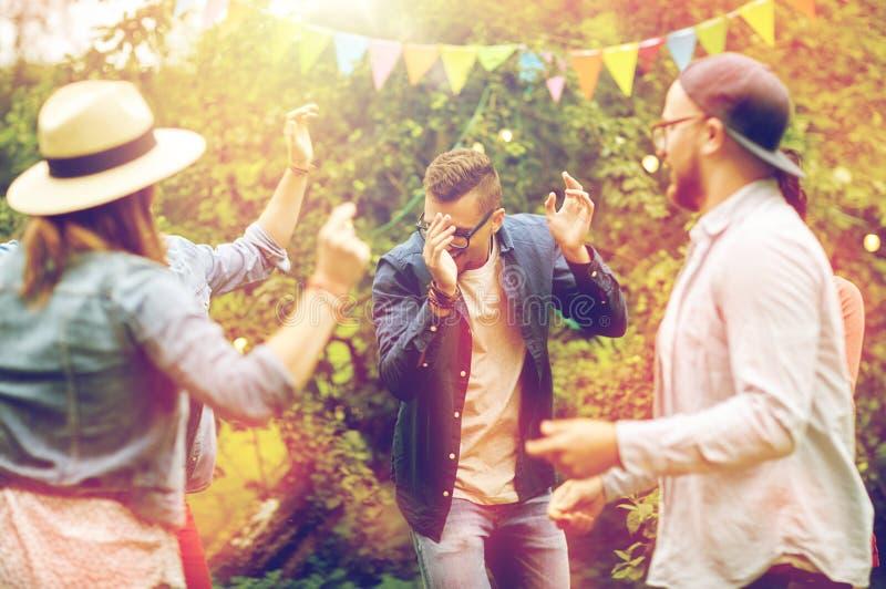 Lyckliga vänner som dansar på sommar, festar i trädgård royaltyfri bild