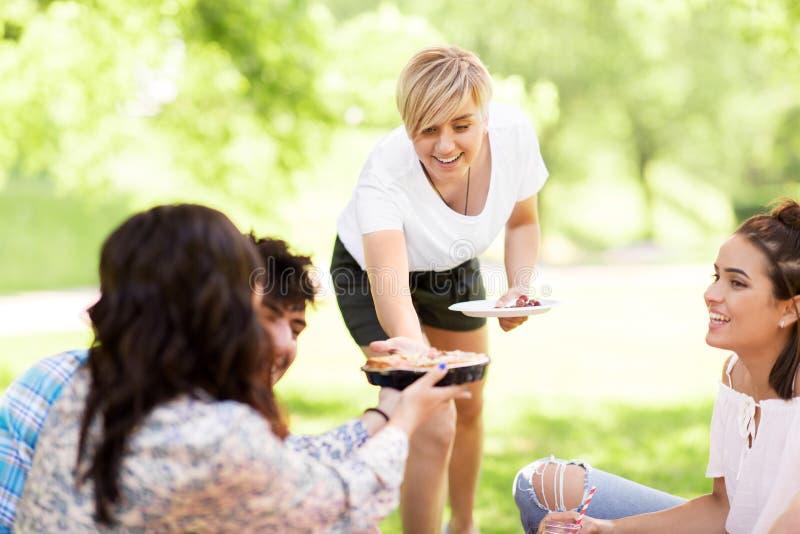 Lyckliga vänner som delar pajen på picknicken i sommar, parkerar royaltyfri foto