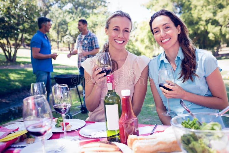 Lyckliga vänner som dricker på parkera royaltyfria foton