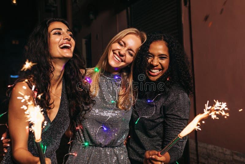 Lyckliga vänner som firar nytt år med tomtebloss på natten royaltyfria bilder