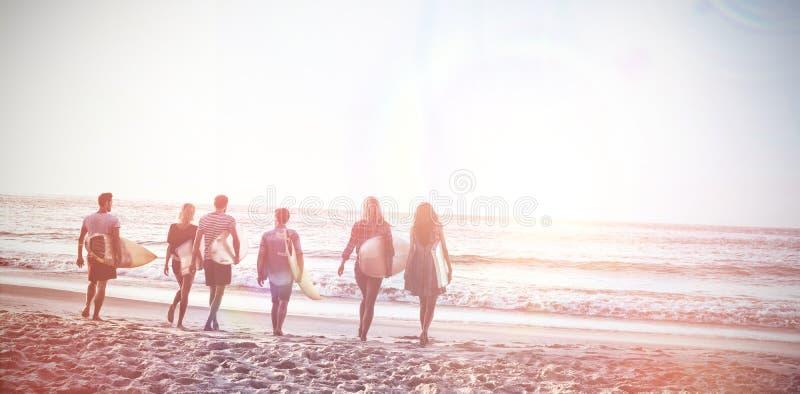 Lyckliga vänner som går med surfingbrädor arkivbilder