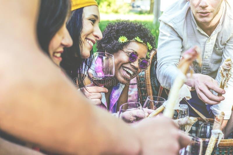 Lyckliga vänner som gör en picknick i, parkerar utomhus- - ungdomarsom tycker om tid som dricker tillsammans rött vin arkivbild