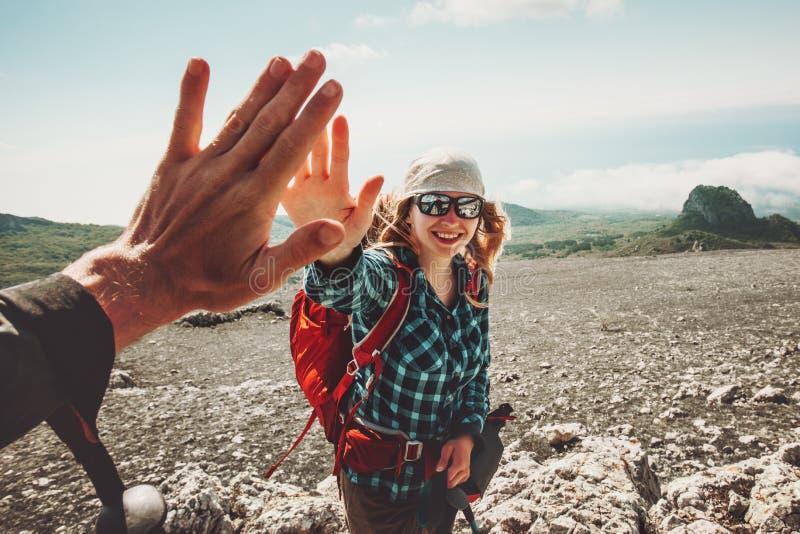 Lyckliga vänner som ger fem händer som reser på berg royaltyfri bild