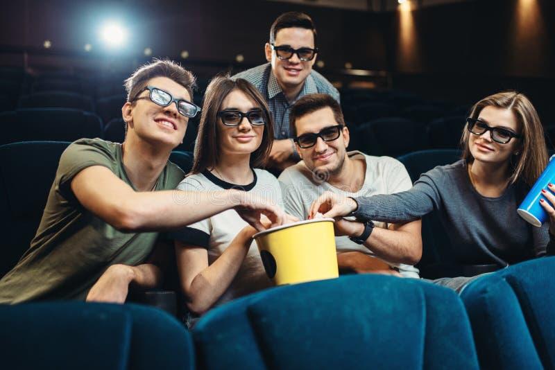Lyckliga vänner som håller ögonen på film i bio royaltyfri fotografi