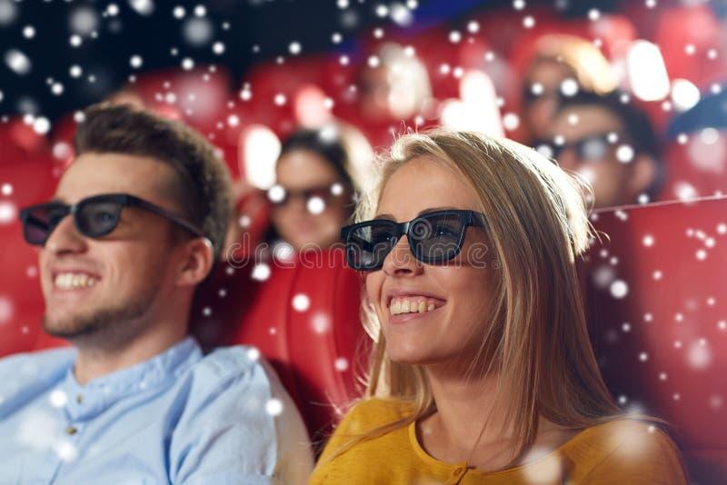 Lyckliga vänner som håller ögonen på film i teatern 3d arkivfoton