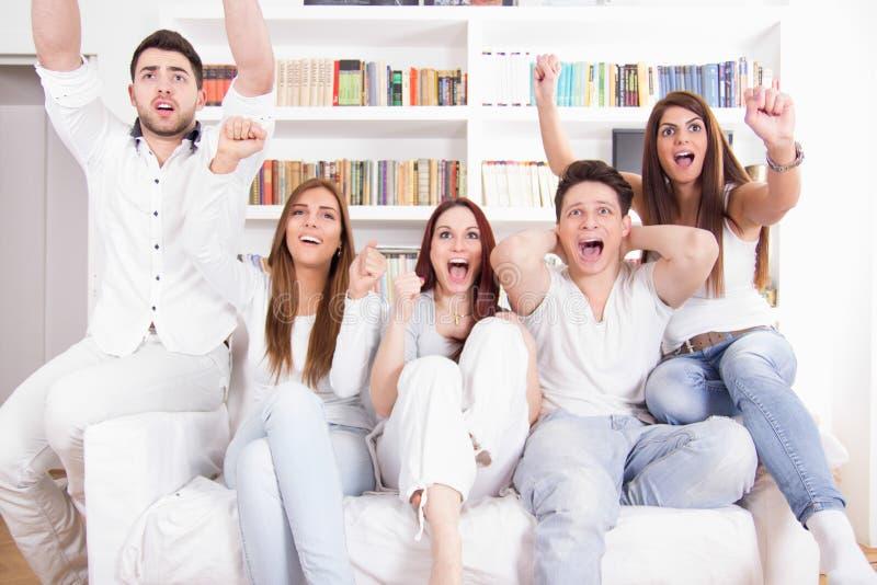 Lyckliga vänner som håller ögonen på fotbollsmatchen på tv royaltyfri fotografi