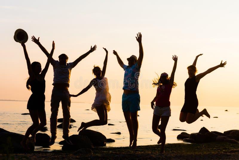 Lyckliga vänner som har ett parti på en strand arkivfoton