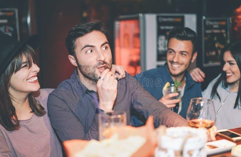 Lyckliga vänner som har gyckel som dricker coctailen i en stång - ungt moderiktigt folk som tillsammans skrattar och tycker om he arkivbild